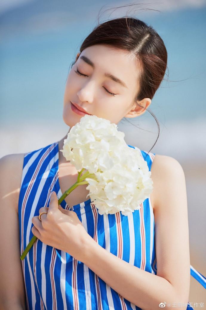 【美天棋牌】王丽坤海边度假 着无袖长裙漫步惬意慵懒